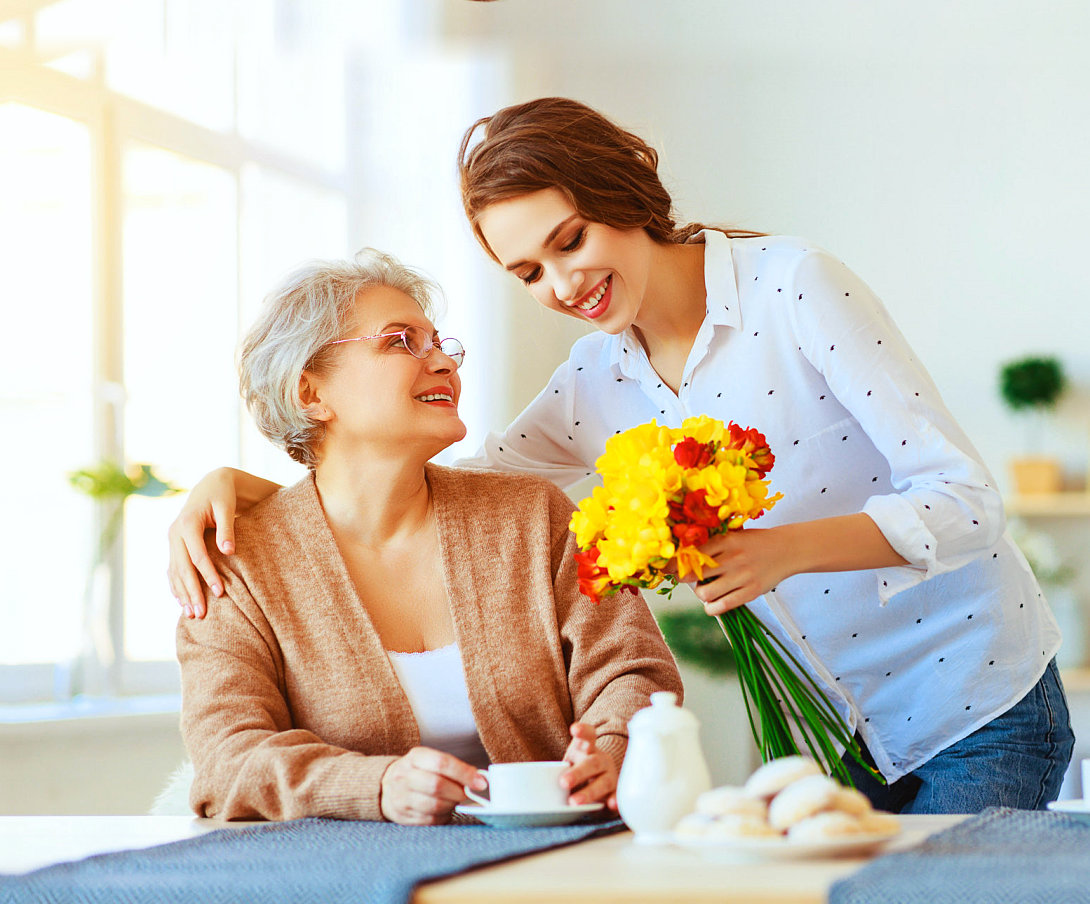 senior woman and caregiver with flowers