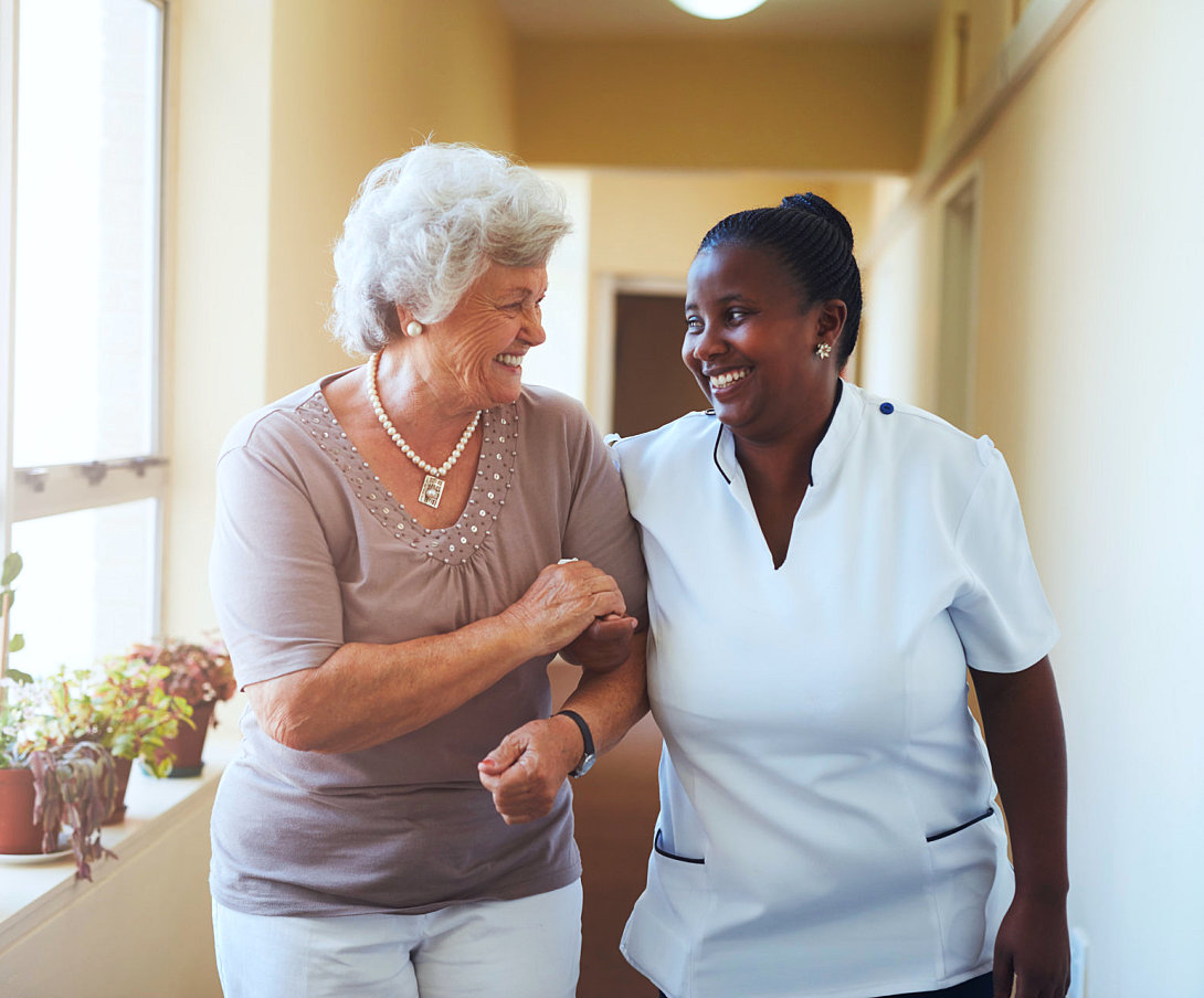 senior woman with caregiver smiling