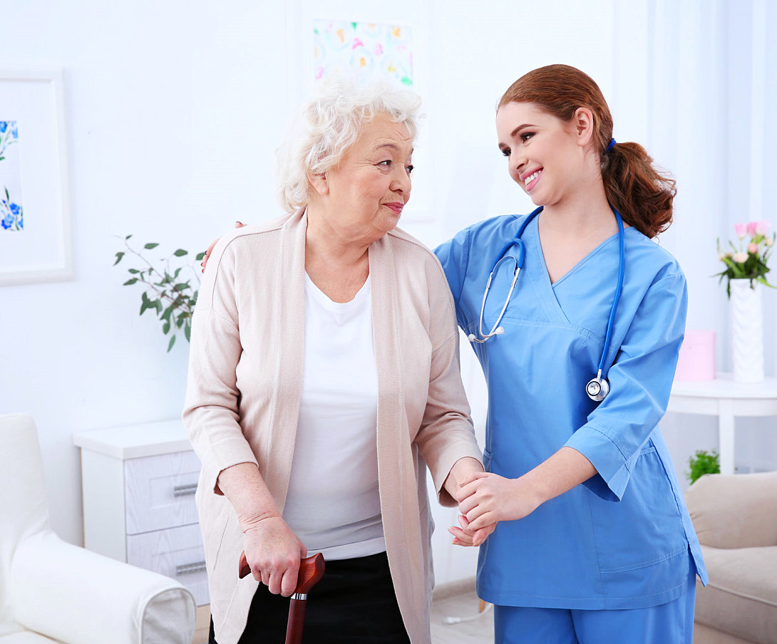senior woman and caregiver smiling wiht each other