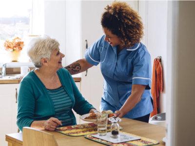 caregiver serving elder woman a meal