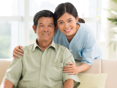 elder man sitting on a couch with caregiver