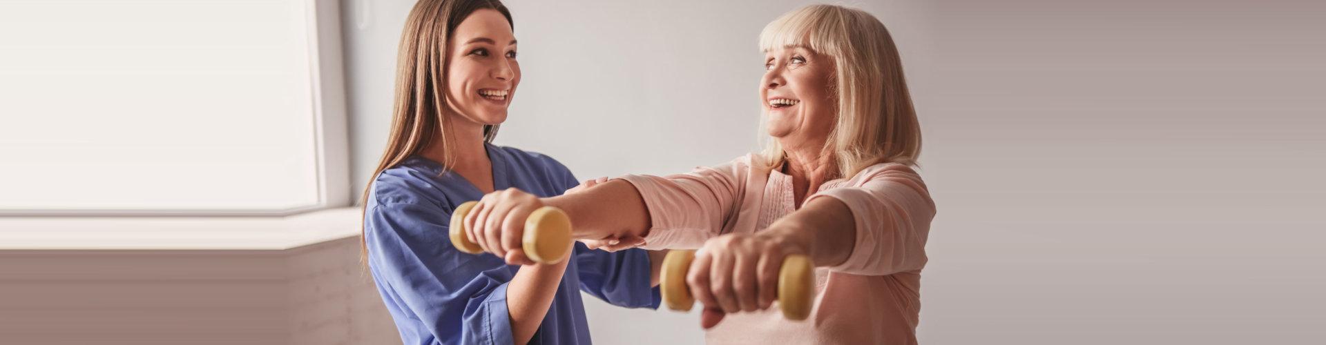 caregiver helping elder woman on exercising